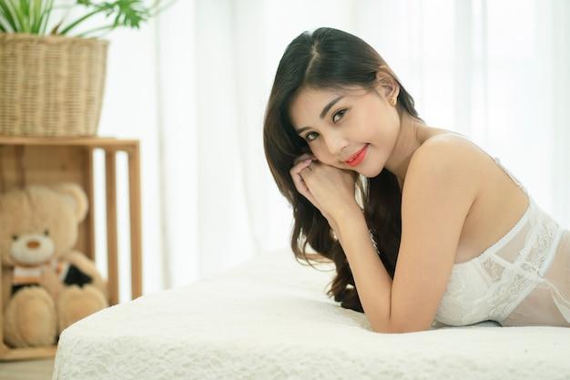 Młoda piękna azjatycka kobieta pozuje w białej seksownej bieliźnie na łóżku.