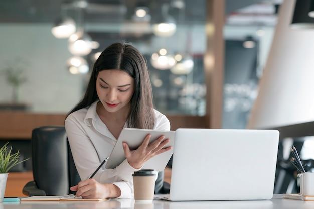 Młoda piękna azjatycka kobieta pracuje na komputerze typu tablet i laptop, siedząc w swoim biurze przy biurku.