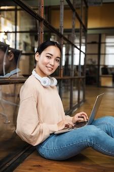 Młoda piękna azjatycka kobieta pracuje na laptopie siedząc na podłodze w biurze