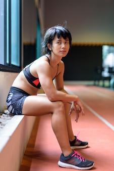 Młoda piękna azjatycka kobieta siedzi i relaks na siłowni