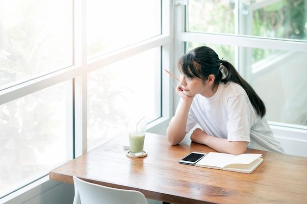 Młoda piękna azjatycka kobieta siedzi z ręką na brodzie, myśląc i patrząc przez okno, relaksując się w kawiarni.