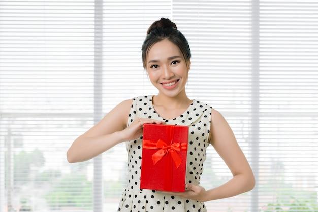Młoda piękna azjatycka kobieta trzyma czerwone pudełko na prezent