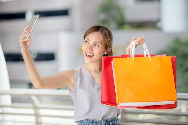 Młoda piękna azjatycka kobieta trzyma jej smartphone brać selfie z jej torba na zakupy w miasto ulicie