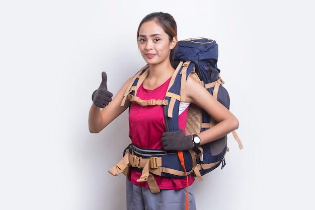 Młoda piękna azjatycka kobieta turysta z plecakiem pokazująca kciuk w górę ok gest na białym tle