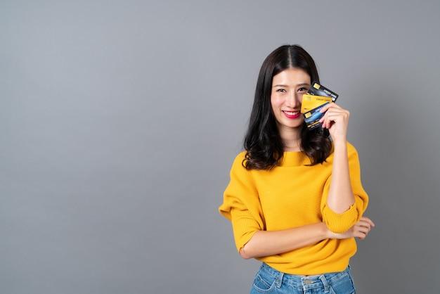 Młoda piękna azjatycka kobieta uśmiecha się i przedstawia w ręku kartę kredytową, pokazując zaufanie i pewność dokonywania płatności