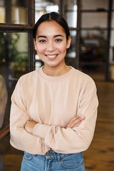 Młoda piękna azjatycka kobieta uśmiecha się i stoi ze skrzyżowanymi rękami podczas pracy w biurze