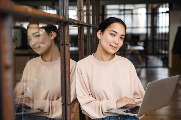 Młoda piękna azjatycka kobieta uśmiecha się i trzyma laptopa podczas pracy w biurze