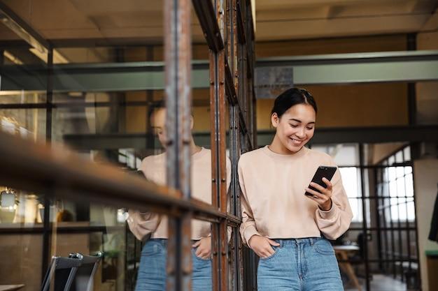 Młoda piękna azjatycka kobieta uśmiecha się i trzyma telefon podczas pracy w biurze