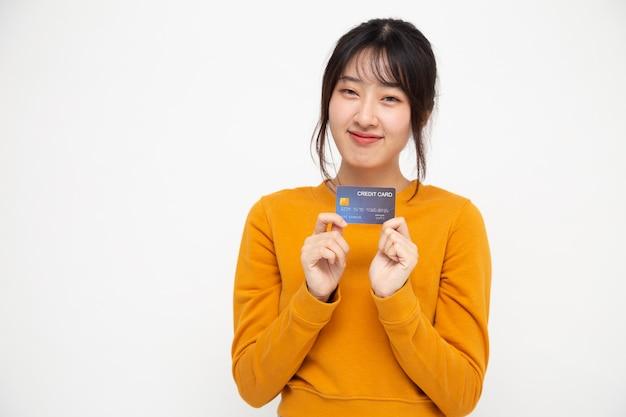 Młoda piękna azjatycka kobieta uśmiechnięta, pokazująca, przedstawiająca kartę kredytową na białym tle, chiński model