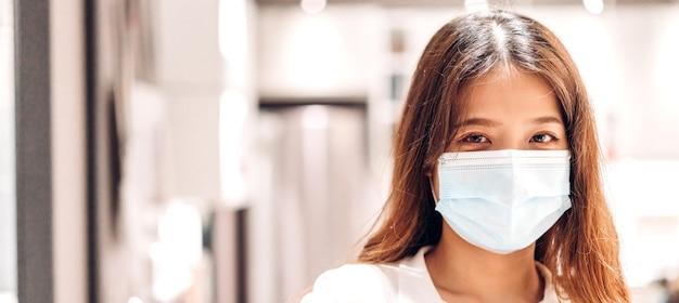 Młoda piękna azjatycka kobieta w kwarantannie dla koronawirusa nosząca maskę chirurgiczną z ochroną twarzy z dystansem społecznym w mieście. koncepcja covid19