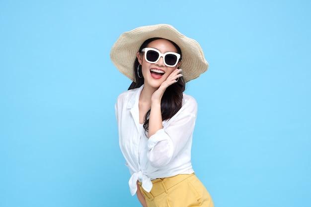 Młoda piękna azjatycka kobieta w letnich ubranie na sobie słomkowy kapelusz, okulary przeciwsłoneczne i powiedzieć coś, usta i uśmiech na na białym tle jasnoniebieskiej ścianie
