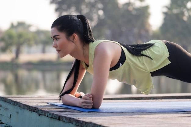 Młoda piękna azjatycka kobieta w strojach sportowych oszalała rano w parku, aby ćwiczyć równowagę i siłę, aby uzyskać zdrowy tryb życia. młoda piękna kobieta lekkoatletycznego robi ćwiczenia deski.