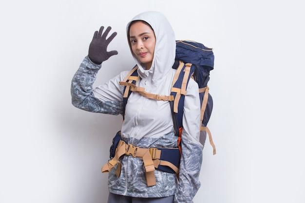 Młoda piękna azjatycka kobieta z plecakiem pokazująca przywitaj się na białym tle