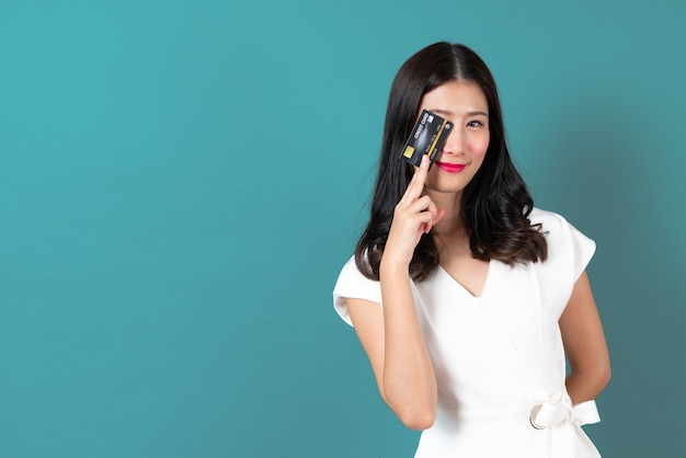 Młoda piękna azjatycka kobieta z radosną buźką i przedstawia w ręku kartę kredytową, pokazując zaufanie i pewność dokonywania płatności na niebiesko