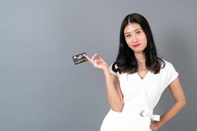 Młoda piękna azjatycka kobieta z radosną buźką i przedstawia w ręku kartę kredytową, pokazując zaufanie i pewność dokonywania płatności na szaro