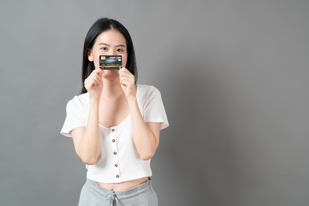Młoda piękna azjatycka kobieta z radosną buźkę i przedstawienie karty kredytowej w ręku, pokazując zaufanie i pewność dokonywania płatności