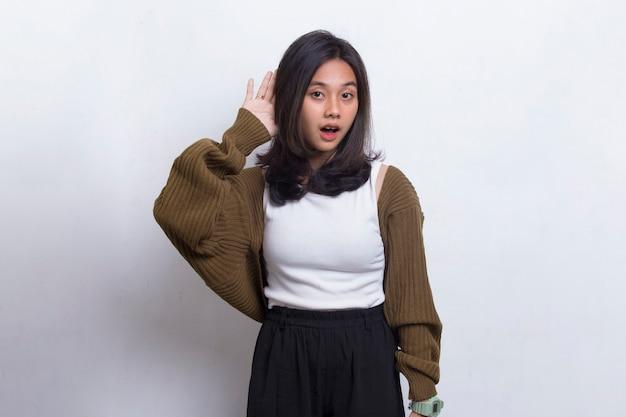 Młoda piękna azjatycka kobieta z ręką na uchu słuchająca przesłuchania plotek na białym tle