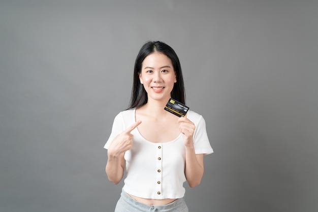 Młoda piękna azjatycka kobieta z szczęśliwą twarzą i prezentującą kartę kredytową w ręku pokazującą zaufanie i pewność siebie do dokonywania płatności