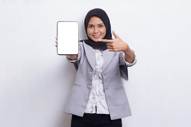 Młoda piękna azjatycka muzułmańska kobieta demonstruje telefon komórkowy na białym tle