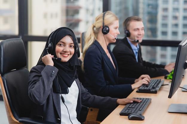 Młoda piękna azjatycka muzułmańska kobieta pracuje usługowego biurka konsultanta obsługi klienta personel opowiada na słuchawki w centrum telefonicznym
