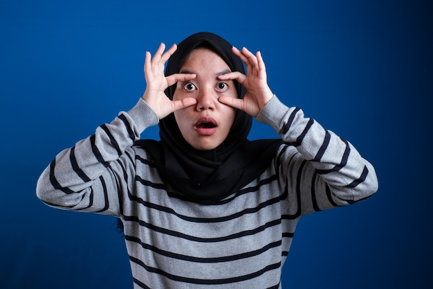 Młoda piękna azjatycka muzułmańska kobieta ubrana w arabski hidżab na białym tle, próbując otworzyć oczy palcami, senna i zmęczona poranne zmęczenie