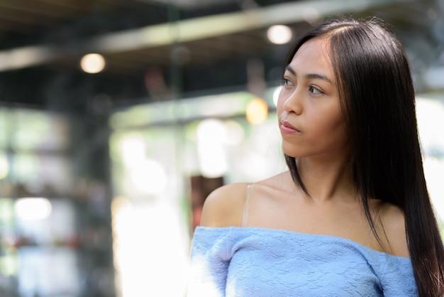 Młoda piękna azjatycka nastolatka myśli na zewnątrz w kawiarni ze szklanymi oknami