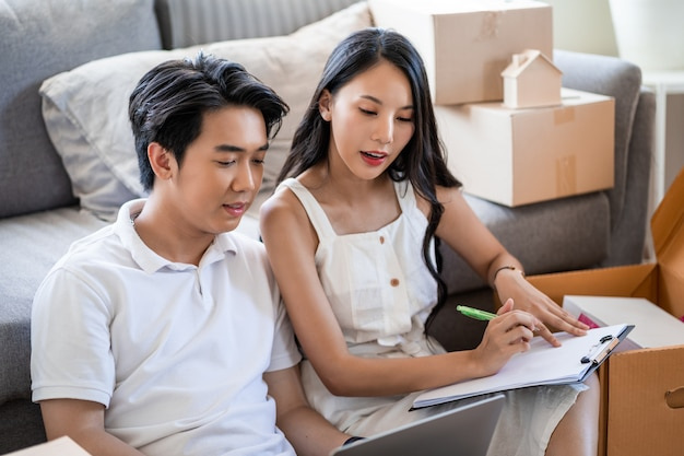 Młoda piękna azjatycka para zakochana przeprowadzka do nowego domu, siedząca na podłodze bardzo szczęśliwa i wesoła dla nowego mieszkania wokół kartonów i trzymająca kartony podczas przeprowadzki