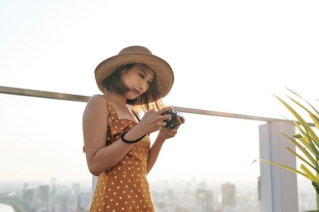Młoda piękna azjatycka podróżniczka, która używa cyfrowego aparatu kompaktowego i uśmiecha się