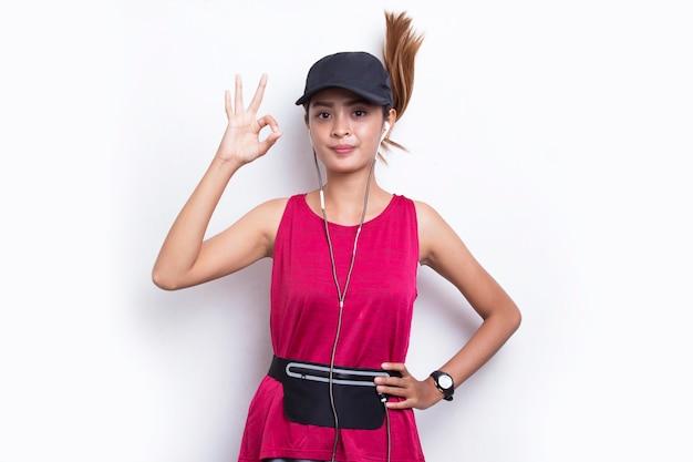 Młoda piękna azjatycka sportowa kobieta pokazująca kciuk w górę ok gest na białym tle