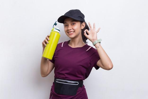 Młoda piękna azjatycka sportowa kobieta wody pitnej po treningu na białym tle