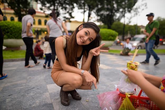 Młoda piękna azjatycka turystka zamawia jedzenie i robi uroczą pozę