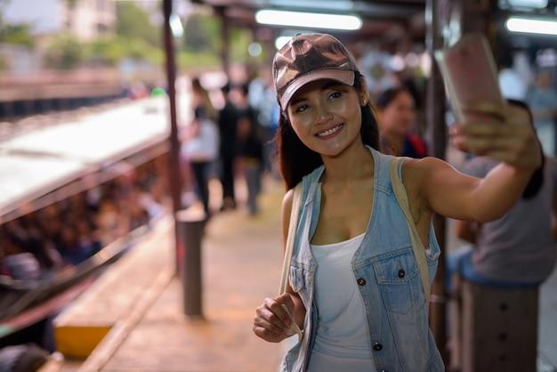 Młoda piękna azjatycka turystyczna kobieta zwiedza miasto