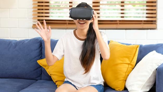 Młoda piękna azjatykcia kobieta ekscytuje w vr słuchawki przyglądającym up i próbuje dotykać przedmioty w rzeczywistość wirtualna w domu żywym pokoju