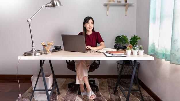 Młoda piękna azjatykcia kobieta pracuje w domu