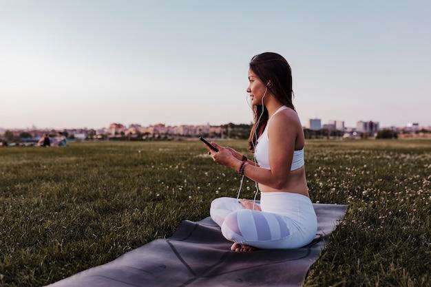 Młoda piękna azjatykcia kobieta relaksująca po jej joga praktyki słucha muzyka na słuchawkach i telefonie komórkowym. joga i koncepcja zdrowego stylu życia