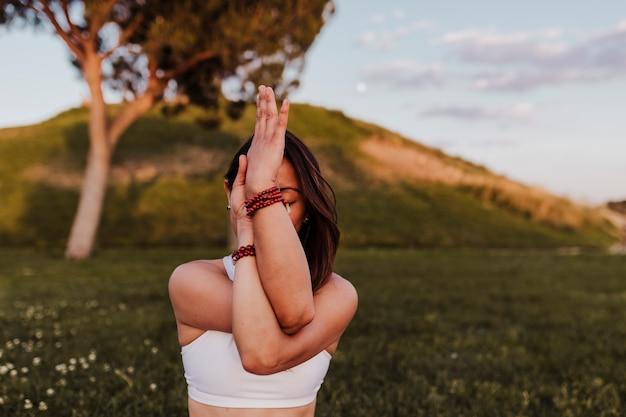 Młoda piękna azjatykcia kobieta robi joga w parku przy zmierzchem.