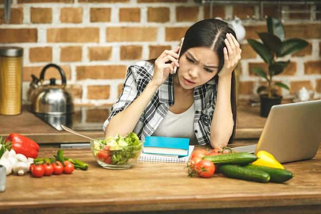 Młoda piękna azjatykcia podkreśliła kobieta z laptopem w kuchni. praca w domu. w stresie.