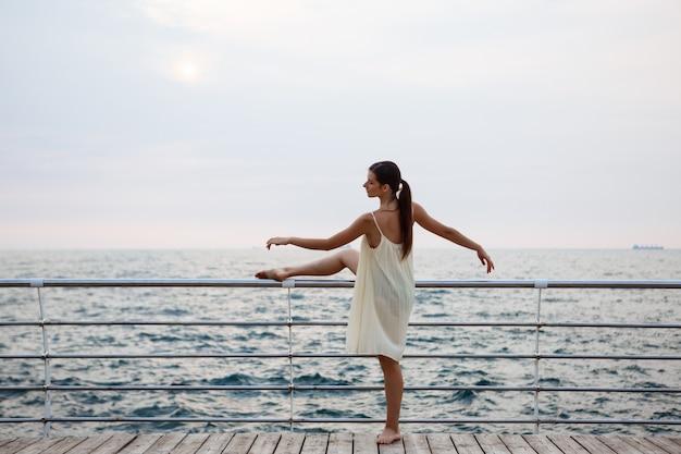 Młoda piękna balerina tańczy i pozuje na zewnątrz