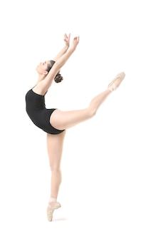 Młoda piękna balerina tańczy na białym tle