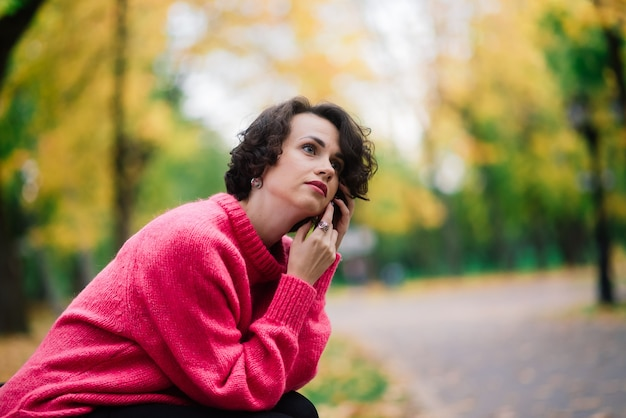 Młoda piękna balerina w jasnym płaszczu i pointe siedzieć na ławce, odpoczywać na świeżym powietrzu w jesiennym parku.