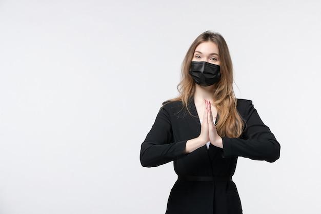 Młoda piękna biznesowa dama w garniturze nosząca maskę chirurgiczną i wykonująca gest podziękowania na odosobnionej białej ścianie
