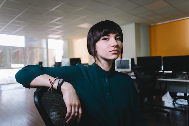 Młoda piękna biznesowa kobieta ono uśmiecha się na tło pracach. dziewczyna lubi swoją pracę biurową