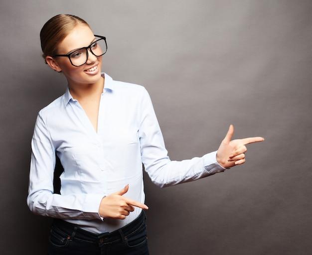 Młoda piękna biznesowa kobieta pokazuje coś fo lub copyspase