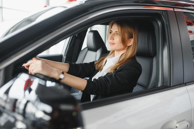 Młoda piękna biznesowa kobieta siedzi w swoim samochodzie