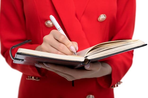 Młoda piękna biznesowa kobieta z notatnikiem i piórem w czerwonym stroju
