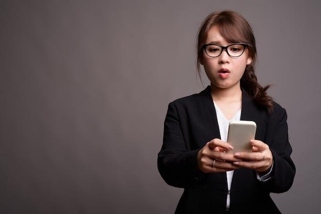 Młoda piękna bizneswoman azjatyckiego przy użyciu telefonu komórkowego