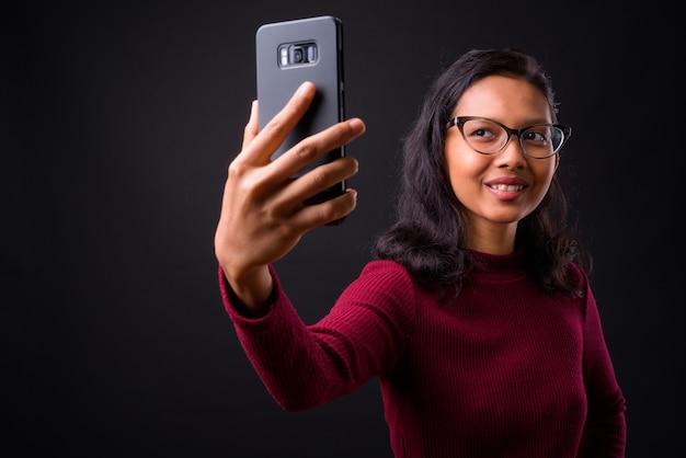Młoda piękna bizneswoman azjatyckiego z kolczykiem w nosie na czarnej ścianie