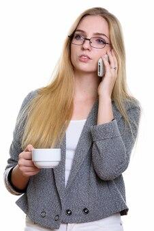 Młoda piękna bizneswoman opowiada na telefonie komórkowym