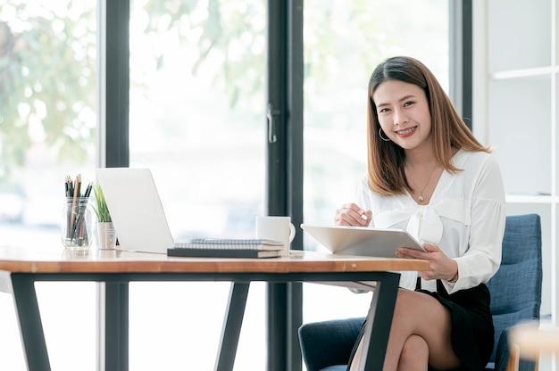 Młoda piękna bizneswoman pracuje na tablecie siedząc przy biurku, uśmiechając się i patrząc na kamery, kopia przestrzeń.