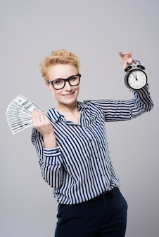Młoda piękna bizneswoman trzyma pieniądze na białym tle